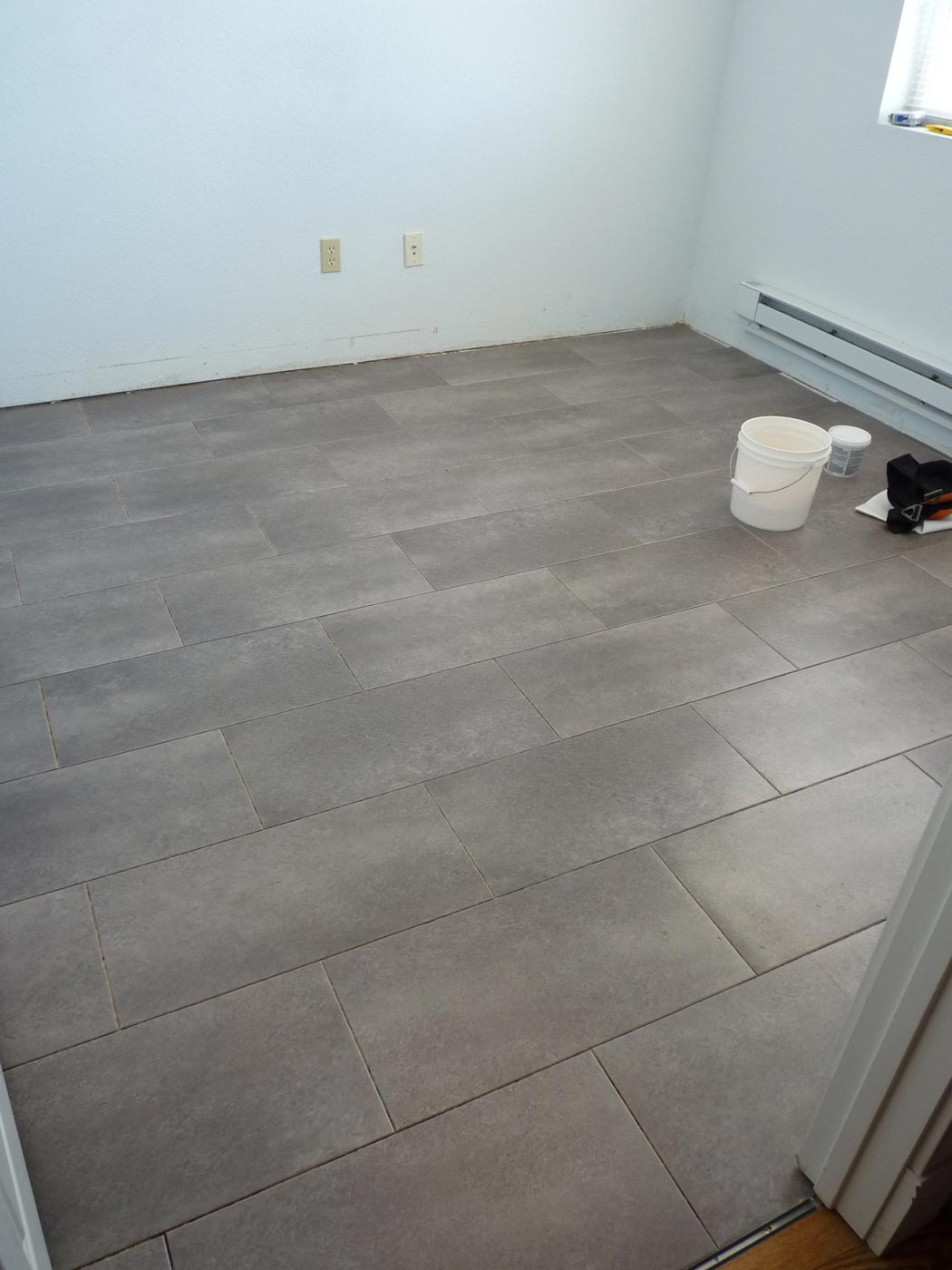 Bedroom makeover 1 part 4 laying the tile cathy graham for Groutable vinyl tile in bathroom